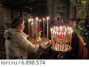 Купить «Женщина ставит свечку на всенощной», эксклюзивное фото № 6898574, снято 6 января 2015 г. (c) Дмитрий Неумоин / Фотобанк Лори