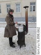 Купить «Коломна, молодой человек в старинной одежде готовит на печи сбитень», эксклюзивное фото № 6898662, снято 8 января 2015 г. (c) Дмитрий Неумоин / Фотобанк Лори