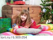 Купить «Девочка играет возле новогодней елки среди разноцветных подушек», фото № 6909054, снято 28 декабря 2014 г. (c) Кекяляйнен Андрей / Фотобанк Лори