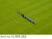 Спортсмены приветствуют друг друга перед фтбольным матчем на зеленом поле. Стоковое фото, фотограф Антон Довбуш / Фотобанк Лори