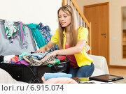 Купить «Girl packing luggage», фото № 6915074, снято 21 апреля 2014 г. (c) Яков Филимонов / Фотобанк Лори