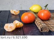 Несколько мандаринов и лимон на циновке и темном фоне. Стоковое фото, фотограф Daodazin / Фотобанк Лори