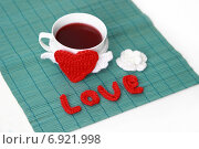 Чашка чая и вязаное сердечко на зелёной бамбуковой салфетке. Стоковое фото, фотограф Анастасия Андрюхина / Фотобанк Лори