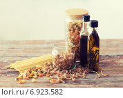 Купить «close up of two olive oil bottles and pasta in jar», фото № 6923582, снято 21 января 2014 г. (c) Syda Productions / Фотобанк Лори