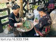 Купить «Две китаянки плетут маленькие корзиночки из тростниковых листьев», фото № 6933194, снято 7 февраля 2014 г. (c) Алексей Маринченко / Фотобанк Лори