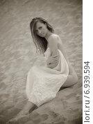 Молодая женщина, сидящая на песке. Стоковое фото, фотограф Evhen Marienko / Фотобанк Лори