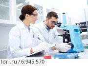 Купить «scientists with clipboard and microscope in lab», фото № 6945570, снято 4 декабря 2014 г. (c) Syda Productions / Фотобанк Лори