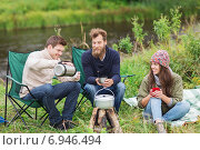 Купить «group of smiling tourists cooking food in camping», фото № 6946494, снято 31 августа 2014 г. (c) Syda Productions / Фотобанк Лори