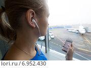 Девушка слушает музыку у окна в аэропорту. Стоковое фото, фотограф Данил Руденко / Фотобанк Лори