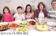 Семья из пяти человек смотрит в камеру, сидя за столом перед семейным ужином. Стоковое видео, видеограф Кекяляйнен Андрей / Фотобанк Лори