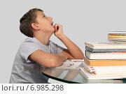 Купить «Мальчик сидит за стеклянным столом в окружении книг и мечтательно смотрит вверх. Изолировано на сером фоне», фото № 6985298, снято 4 февраля 2015 г. (c) Дмитрий Боков / Фотобанк Лори