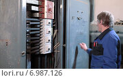 Купить «Высоковольтный электрический блок управления с переключателями и электрик-работник инспекции», видеоролик № 6987126, снято 10 января 2015 г. (c) Кекяляйнен Андрей / Фотобанк Лори
