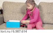 Купить «Девочка играет в игрушки на диване», видеоролик № 6987614, снято 12 января 2015 г. (c) Кекяляйнен Андрей / Фотобанк Лори
