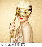 Beautiful young woman in mysterious golden Venetian mask. Стоковое фото, агентство Ingram Publishing / Фотобанк Лори
