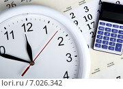 Настенные круглые механические часы и калькулятор на листе календаря. Стоковое фото, фотограф Александр Калугин / Фотобанк Лори