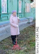 Купить «Пожилая женщина наводит порядок в палисаднике», фото № 7041942, снято 2 ноября 2014 г. (c) Марина Славина / Фотобанк Лори