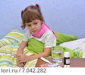Купить «Маленькая больная девочка сидит в кровати  и грустно смотрит на лекарства», фото № 7042282, снято 25 января 2015 г. (c) Ирина Борсученко / Фотобанк Лори