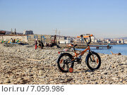 Детский велосипед стоит на галечном пляже (2015 год). Редакционное фото, фотограф Дмитрий Шанько / Фотобанк Лори