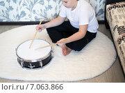Купить «Подросток играет на барабане дома, сидя на полу», фото № 7063866, снято 25 февраля 2015 г. (c) Володина Ольга / Фотобанк Лори