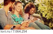 Купить «Hipsters using their smartphones in park», видеоролик № 7064254, снято 19 августа 2019 г. (c) Wavebreak Media / Фотобанк Лори