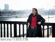 Обаятельный молодой человек стоит на мосту облокотившись на ограждение и щурится на солнце. Стоковое фото, фотограф Анастасия Кузьмина / Фотобанк Лори