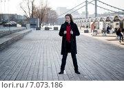 Молодой мужчина на фоне выставки возле ЦДХ и Крымского моста в Москве, ранняя весна. Стоковое фото, фотограф Анастасия Кузьмина / Фотобанк Лори