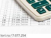 Купить «Покупка квартиры с помощью ипотеки. Калькулятор лежит на графике платежей кредитного договора», эксклюзивное фото № 7077254, снято 2 марта 2015 г. (c) Игорь Низов / Фотобанк Лори