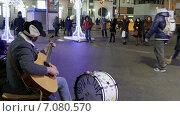 Уличный музыкант играет на гитаре и бас-барабане около метро. Москва, зимний вечер (2015 год). Редакционное видео, видеограф Арташес Оганджанян / Фотобанк Лори