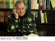 Мужчина сидит за столом и говорит по телефону. Стоковое фото, фотограф Татьяна Кузьмина / Фотобанк Лори
