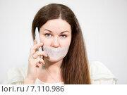 Купить «Женщина с грустными глазами с заклеенным ртом и мобильным телефоном», фото № 7110986, снято 28 февраля 2015 г. (c) Кекяляйнен Андрей / Фотобанк Лори