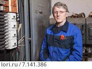 Купить «Мужчина электрик стоит около высоковольтного щитка», фото № 7141386, снято 22 декабря 2014 г. (c) Кекяляйнен Андрей / Фотобанк Лори