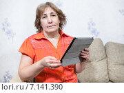 Купить «Женщина с планшетом сидит на диване и смотрит в камеру», фото № 7141390, снято 24 декабря 2014 г. (c) Кекяляйнен Андрей / Фотобанк Лори