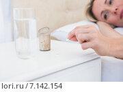 Купить «Pretty blonde lying bed taking pills on bedside table», фото № 7142154, снято 2 октября 2014 г. (c) Wavebreak Media / Фотобанк Лори