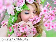 Купить «Красивая девушка в зеленом платье и венке из цветов позирует рядом с цветущей персиковой веткой», фото № 7166342, снято 22 апреля 2019 г. (c) Elena Kucherenko / Фотобанк Лори