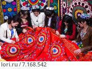 Традиционный праздничный девичник, где девушки вышивают красивый платок на улице в центральном парке Наврузгох во время празднования Навруза (Новый год) в городе Худжанд, Таджикистан (2015 год). Редакционное фото, фотограф Николай Винокуров / Фотобанк Лори