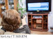 Купить «Женщина переключает каналы телевизора с помощью пульта», фото № 7169874, снято 22 декабря 2014 г. (c) Кекяляйнен Андрей / Фотобанк Лори