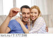 smiling couple showing keys over room background. Стоковое фото, фотограф Syda Productions / Фотобанк Лори