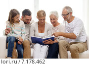 Купить «happy family with book or photo album at home», фото № 7178462, снято 21 августа 2014 г. (c) Syda Productions / Фотобанк Лори
