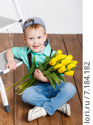 Купить «A boy in a baseball cap with a bouquet of flowers, yellow tulips», фото № 7184182, снято 13 ноября 2019 г. (c) Александр Савченко / Фотобанк Лори