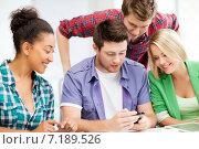 Купить «students looking at smartphone at school», фото № 7189526, снято 16 июня 2013 г. (c) Syda Productions / Фотобанк Лори