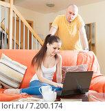 Купить «Семейный конфликт. Девушка сидит на диване с ноутбуком, недовольный мужчины стоит за ее спиной», фото № 7200174, снято 26 мая 2020 г. (c) Дарья Филимонова / Фотобанк Лори
