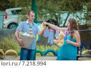 Купить «Мужчина и беременная женщина развешивают детскую одежду», фото № 7218994, снято 18 августа 2013 г. (c) Наталья Давыдова / Фотобанк Лори