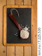 Купить «Рис арборио в старой деревянной ложке на маленькой меловой доске», фото № 7225530, снято 1 апреля 2015 г. (c) Лидия Рыженко / Фотобанк Лори