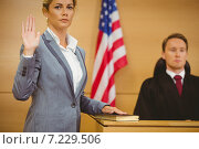 Witness swearing on the bible telling the truth. Стоковое фото, агентство Wavebreak Media / Фотобанк Лори