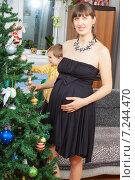 Купить «Улыбающаяся беременная женщина, одетая в черное платье, украшает рождественскую ель», фото № 7244470, снято 18 января 2015 г. (c) Сергей Дубров / Фотобанк Лори