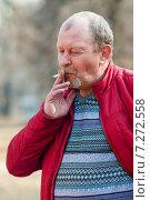 Купить «Мужчина в красной куртке курит сигарету на прогулке», эксклюзивное фото № 7272558, снято 12 апреля 2015 г. (c) Игорь Низов / Фотобанк Лори