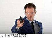 Купить «Мужчина в деловом костюме направил револьвер в сторону зрителя, лицо в фокусе», фото № 7288778, снято 19 апреля 2015 г. (c) Ивашков Александр / Фотобанк Лори