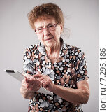 Old woman holding a tablet in the hands of. Стоковое фото, фотограф Гладских Татьяна / Фотобанк Лори