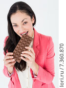 Smiling brunette biting bar of chocolate. Стоковое фото, агентство Wavebreak Media / Фотобанк Лори