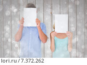 Composite image of young couple holding pages over their faces. Стоковое фото, агентство Wavebreak Media / Фотобанк Лори